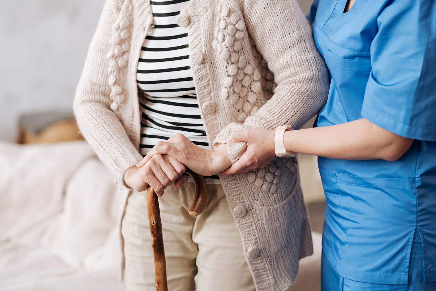 Nurse assisting elder woman with walking